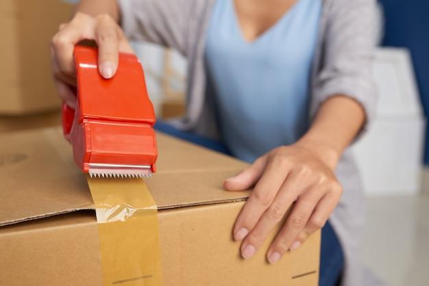 Vrouw verpakking doos met tape