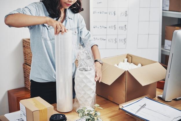Vrouw verpakkingsorder in doos