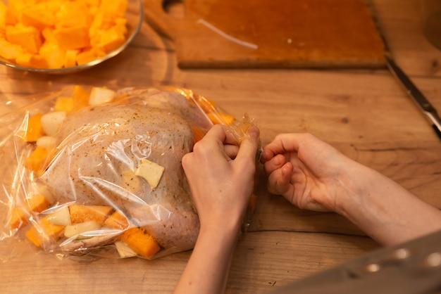Vrouw verpakt kip gemarineerd met kruiden in bakmouw