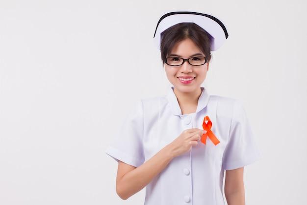 Vrouw verpleegster hand met oranje lint boog, adhd, leukemie, nierkanker bewustzijn symbool, oranje lint voor medische, verpleegkundige liefdadigheid fondsenwerving concept voor nierkanker, adhd, leukemie