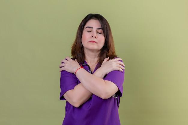 Vrouw verpleegster van middelbare leeftijd uniform dragen en met een stethoscoop knuffelen zichzelf gelukkig en positief met gesloten ogen over groene muur