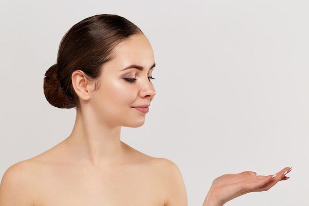 Vrouw verrassing product tonen. mooi meisje expressief wijzen naar de kant. uw advertentie presenteren. expressieve gezichtsuitdrukkingen