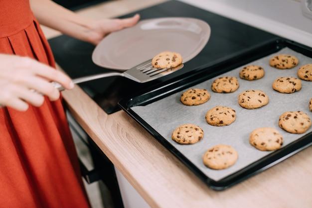 Vrouw verschuift versgebakken koekjes van pan op plaat