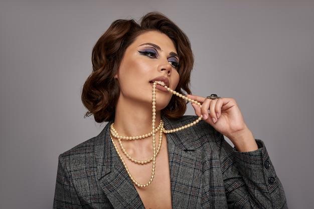 Vrouw versierd met parels. sieraden op de nek en handen, vingers. op een grijze muur in een jasje. concept voor juweliers.