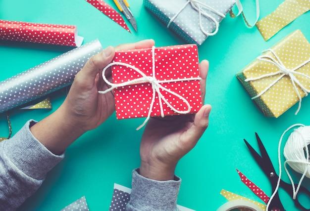 Vrouw versieren leuke geschenkdoos presenteert op werktafel achtergrond