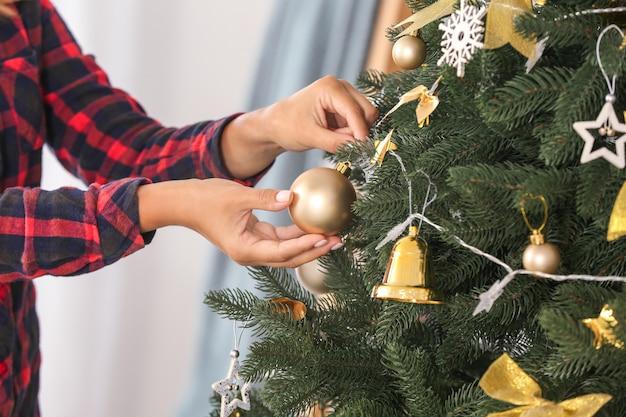 Vrouw versieren mooie kerstboom, close-up