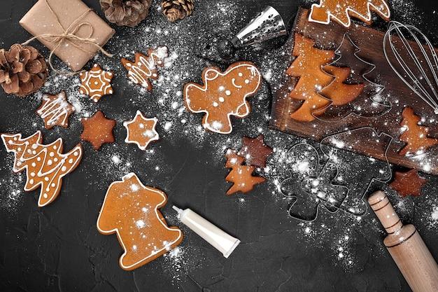 Vrouw versieren peperkoek kerstkoekjes met poedersuiker op donkere achtergrond. vakantie, feest en kookconcept. kerst voorbereidingen concept. bovenaanzicht met kopie ruimte.