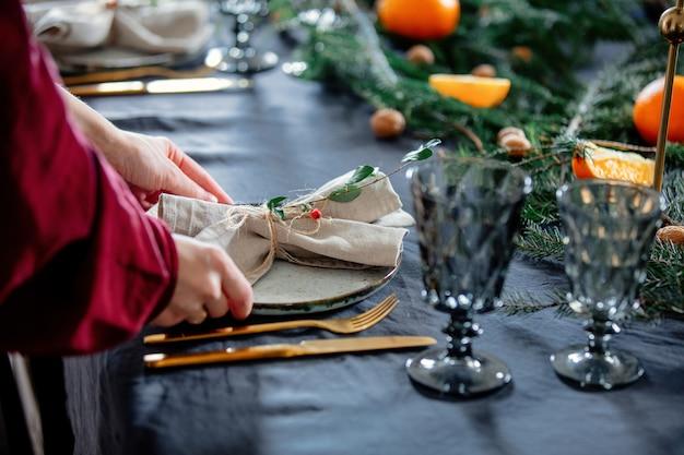 Vrouw versiert een feestelijke tafel voor kerst