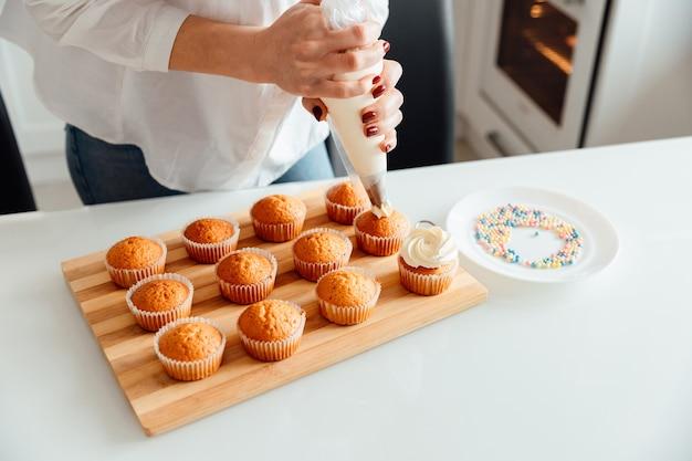 Vrouw versiert versgebakken cupcakes met slagroom