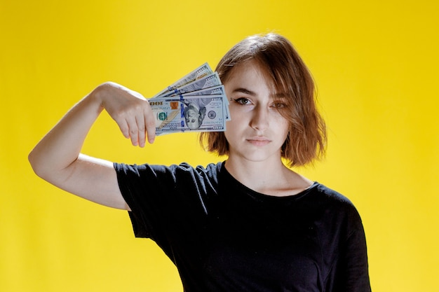 Vrouw verstopt achter een bos geldbankbiljetten en viert feest op gele achtergrond.