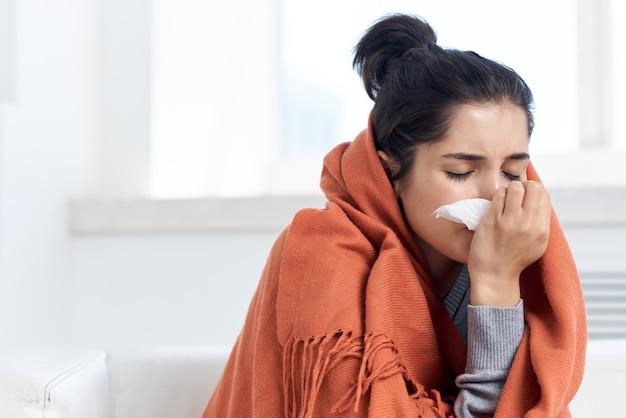 Vrouw verstopt zich met een deken thuis die pillen drinkt behandeling van infectie