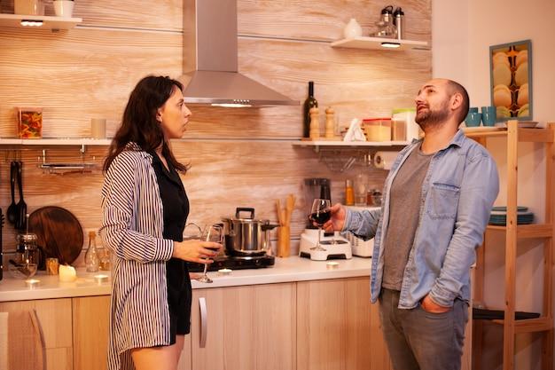 Vrouw vertelt een verhaal aan haar man terwijl ze een glas wijn vasthoudt in de keuken. volwassen paar thuis, rode wijn drinken, praten, glimlachen, genieten van de maaltijd in de eetkamer.
