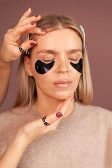 Vrouw verticaal portret met gesloten ogen en patches onder de ogen met hydrogel