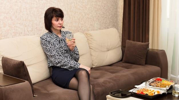 Vrouw verveeld thuis aan tafel met glas witte wijn, eenzaamheid concept