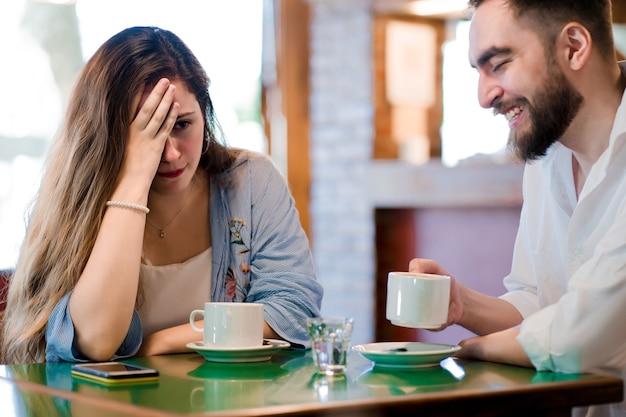 Vrouw verveelt zich op een date in een coffeeshop.
