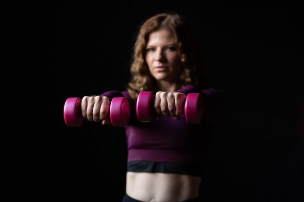 Vrouw, vervelend, sportkleding, met, roze, dumbbells, in, handen, geïsoleerde, op, zwarte achtergrond
