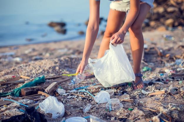 Vrouw verzamelt afval op het strand. milieubescherming concept