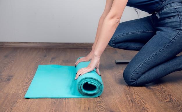 Vrouw verzamelt yogamat op de grond