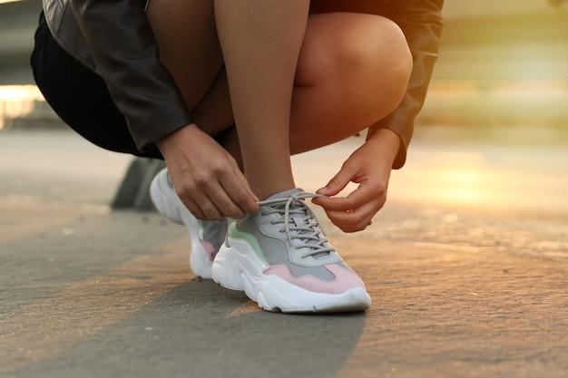 Vrouw veters op sneakers op straat binden