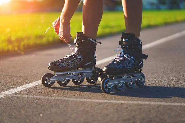 Vrouw veters rolschaatsen voor inline skaten. tiener skaten buitenshuis.
