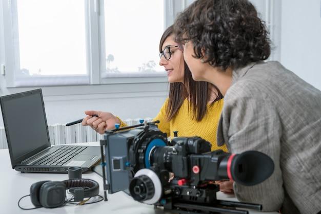 Vrouw video-editor en jonge assistent met behulp van grafische tablet