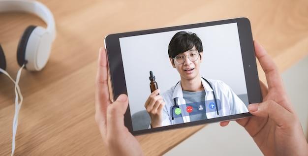 Vrouw videogesprek voeren met arts op tablet en hulp online counseling bieden. concept werken vanuit huis.