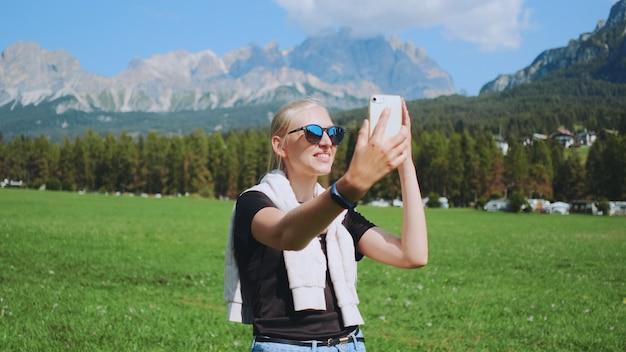 Vrouw videogesprek voeren vanuit het prachtige natuurpark voor bergen. ze deelt indrukken van haar reis.