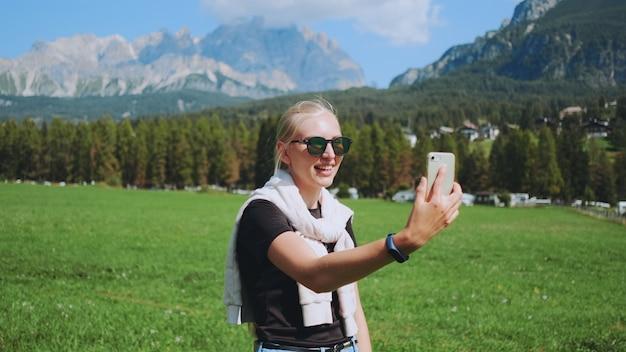 Vrouw videogesprek voeren vanuit prachtige natuurpark tegenover bergen. ze deelt indrukken van haar reis.
