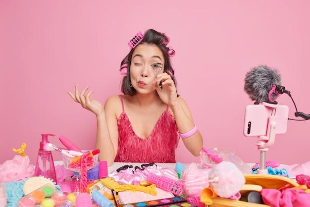 Vrouw videokanaal gastheer ervaren schoonheidsspecialist gebruikt wimpers krultang vertelt over het aanbrengen van make-up presenteert cosmetica onine draagt haarrollers roze jurk poseert binnen.