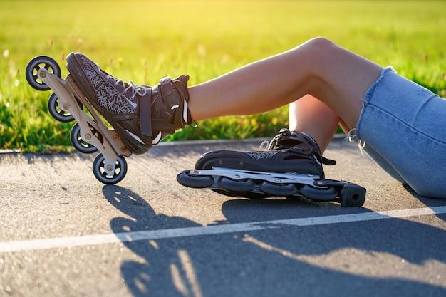 Vrouw viel op asfalt tijdens skaten. inline skaten zonder bescherming