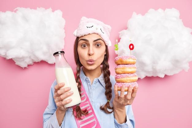 Vrouw viert verjaardag houdt geglazuurde donuts met kaarsen en fles melk gekleed in huishoudelijke kleding poseert binnenshuis thuis