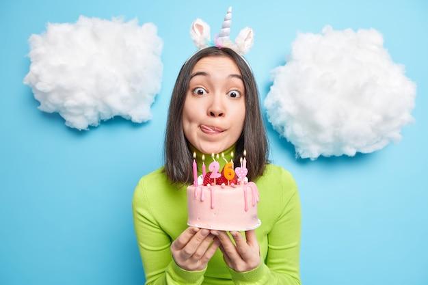 Vrouw viert verjaardag houdt taart vast met brandende kaarsen likt lippen heeft verbaasde uitdrukking draagt groene coltrui en eenhoorn hoofdband