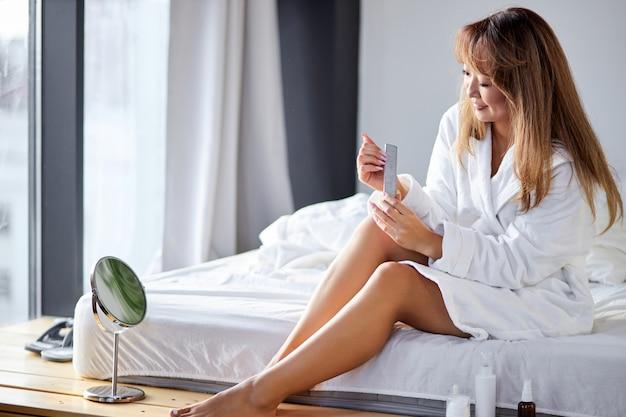 Vrouw vijlt haar nagels met een vijl zittend op het bed in badjas thuis na het douchen, zorgt voor zichzelf, beauty concept.