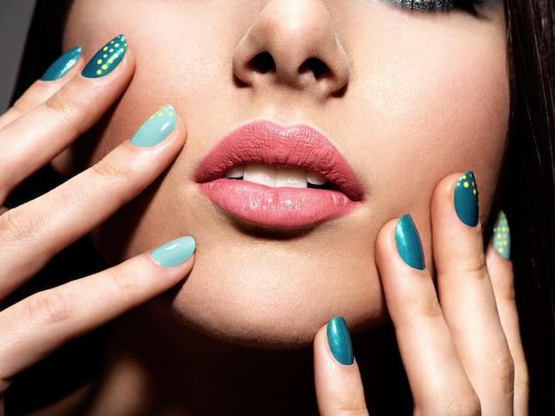 Vrouw vingers met motton blauwe kleur van de nagels op het gezicht