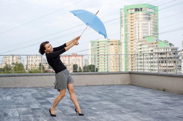 Vrouw vliegt met paraplu, houdt paraplu