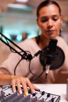 Vrouw vlogger neemt podcast op in thuisstudio verlicht met neonlicht