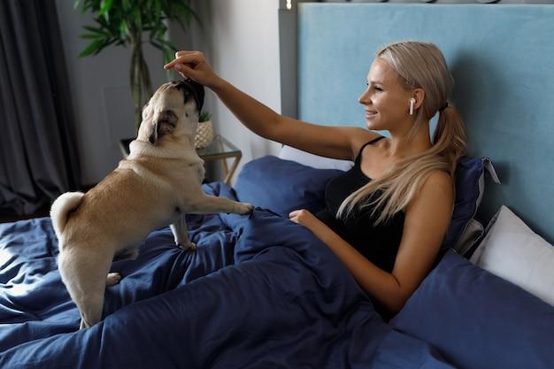 Vrouw voedt de hond terwijl ze 's ochtends in bed ligt.