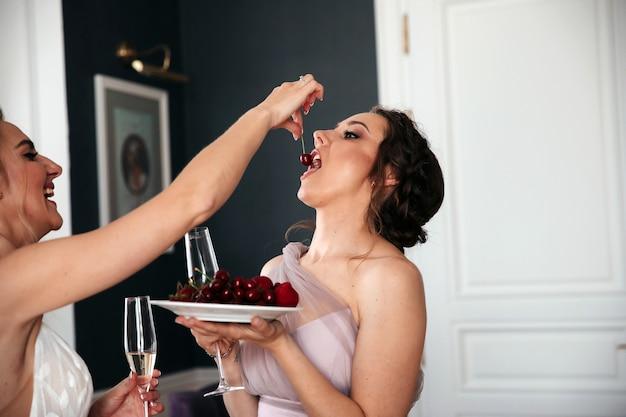 Vrouw voedt een andere vrouw de kers, ze hebben plezier