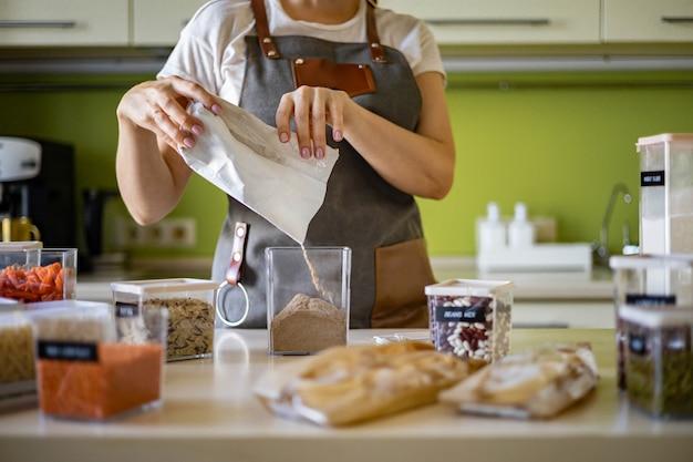 Vrouw voegt gezonde erwtenpasta toe aan transparante opbergdoos in de keuken