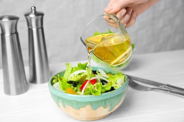 Vrouw voegt smakelijke appelazijn toe aan salade met groenten op tafel
