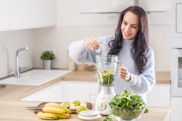 Vrouw voegt water toe aan een mixer voor een smoothie van spinazie, banaan en appel.