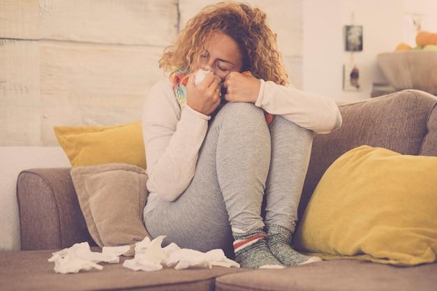 Vrouw voelt koud, ijskoud, met servet in een hand, gewikkeld in deken, zittend op de bank. ongelukkige overstuur vermoeide vrouw lijdt aan een verkoudheid en gebruikt servetten - met een kopje/mok