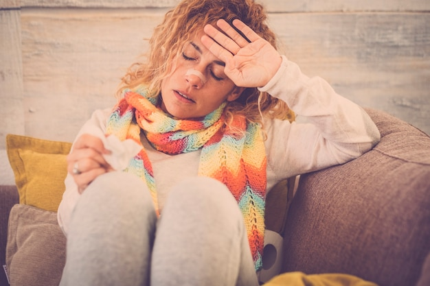 Vrouw voelt koud, ijskoud, met servet in een hand, gewikkeld in deken, zittend op de bank. ongelukkige overstuur vermoeide vrouw zit thuis op een bank