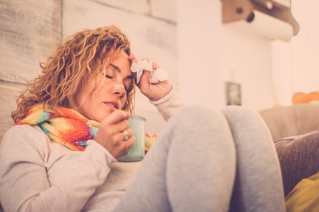 Vrouw voelt koud, ijskoud, met servet in een hand, gewikkeld in deken, zittend op de bank. ongelukkige, vermoeide vrouw zit thuis op een bank die verkouden is en servetten gebruikt