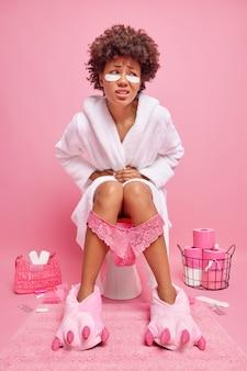 Vrouw voelt pijn met constipatie lijdt aan hevige buikpijn draagt witte zachte badjas brengt pleisters onder de ogen aan heeft kanten broek op benen getrokken poseert in toilet