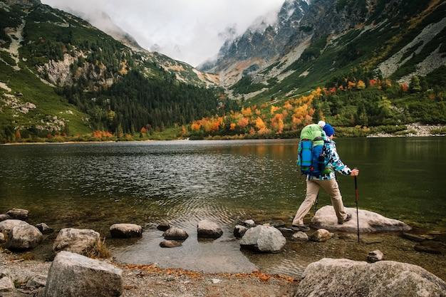 Vrouw voelt vrijheid en geniet van gouden herfst natuur in berg