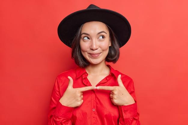 Vrouw voelt zich besluiteloos voordat ze riskante vraaggebaren stelt en wegkijkt draagt stijlvolle zwarte hoed en shirt poseert op levendig rood