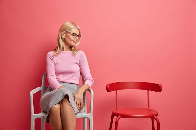 Vrouw voelt zich eenzaam thuis gefocust op lege stoel heeft gebrek aan communicatie draagt casual trui en rok geïsoleerd op roze