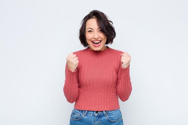Vrouw voelt zich geschokt, opgewonden en blij, lacht en viert succes en zegt wow!