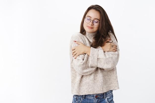 Vrouw voelt zich geweldig in zachte, knusse trui tijdens koud weer, knuffelt zichzelf en glimlacht van comfort en verrukking sluit de ogen, genietend van warme outfit op koude herfstavond over grijze muur.